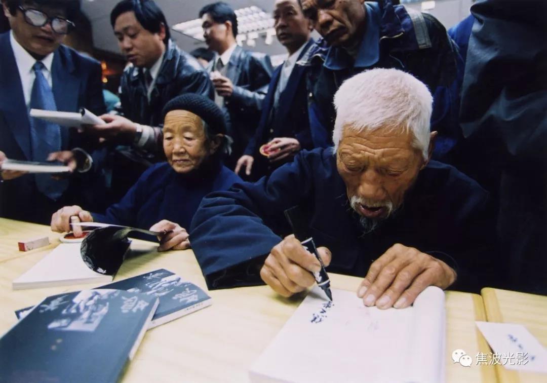 4. 爹娘为观众签名售书。爹工工整整写上自己的名字,娘在书上盖上刻着她和爹名字的鸳鸯章。(1998).jpg