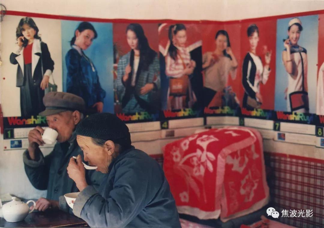 """18. 爹娘每天同桌吃饭。他们身后的墙上张贴的是上世纪八十年代时兴的美人头挂历。""""这些闺女多俊啊,拆开并排贴在墙上好看。你爹说城里人家都是这样。""""娘说。(1988).jpg"""