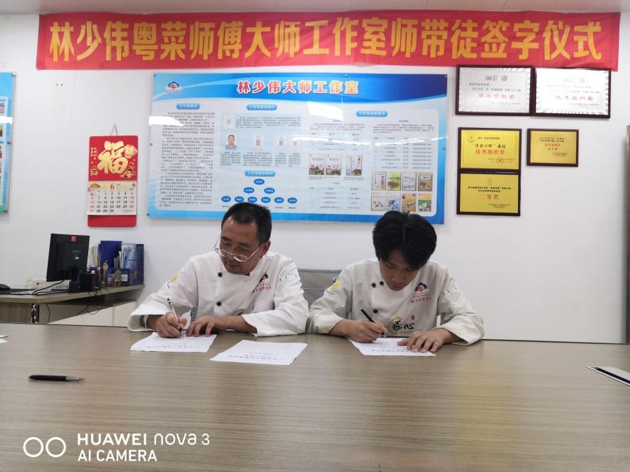 禤建新师傅(左)与徒弟签约.jpg